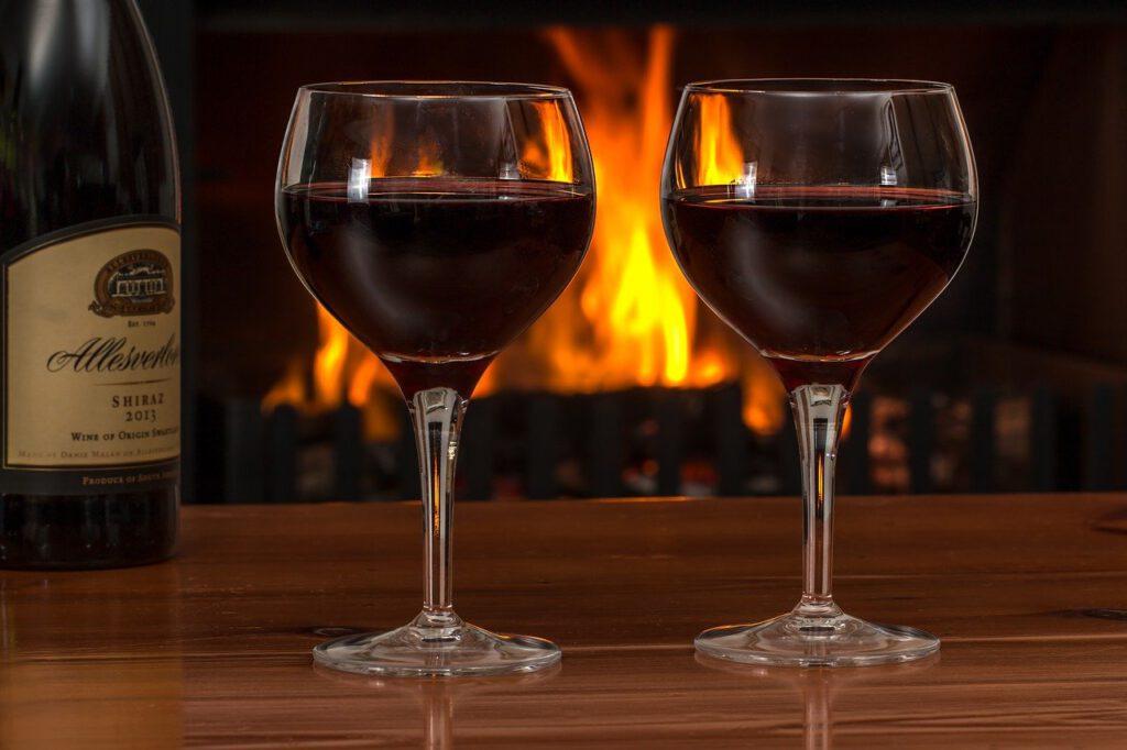 red wine, glasses, log fire